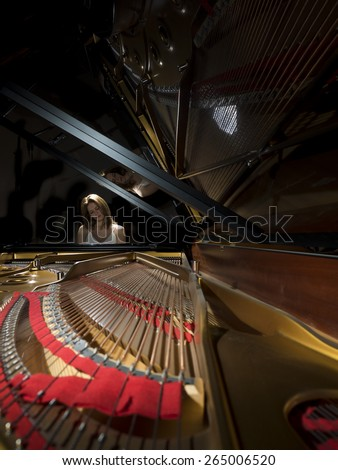 Female pianist performing on a grand concert piano - stock photo