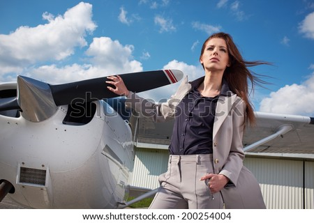 Female pilot preparing for a flight in a light aircraft  - stock photo