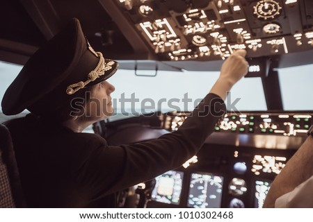 Female pilot the captain of the plane prepares for take-off in the plane cockpit. Girl pilot in uniform flying craft plane in the sky
