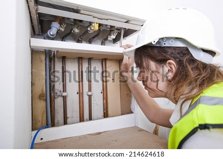 Female plumber examining pipes of central heating boiler - stock photo