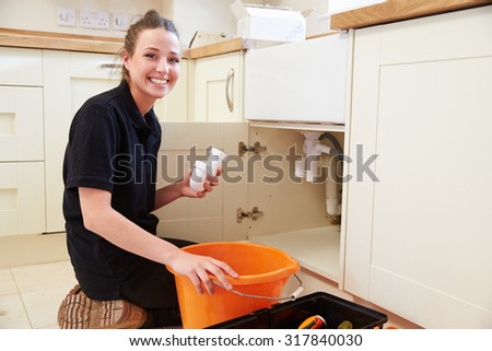 female plumber holding a u bend pipe for a kitchen sink - Kitchen Sink U Bend