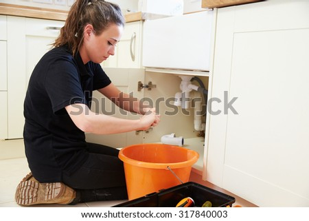 Female plumber preparing a pipe for a kitchen sink