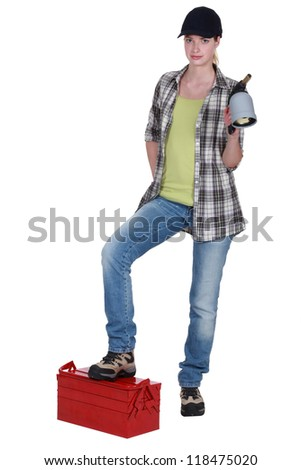 female plumber with foot resting on toolbox - stock photo