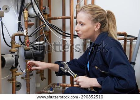 Female Plumber Working On Central Heating Boiler - stock photo