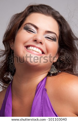 Female Plus size model posing in the studio, face portrait, on grey background. The woman is smiling in a happy manner. Good for concept of health, happiness, dieting, obesity, weight loss. - stock photo