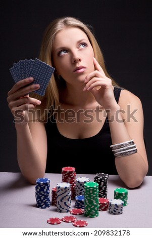 female poker player in casino with cards and chips over grey