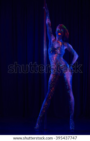 Female pole dancer in bright neon colours under ultraviolet (UV) light on background