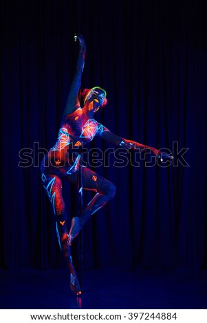 Female pole dancer in bright neon colours under ultraviolet (UV) light on background - stock photo