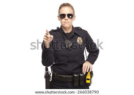 Female police officer in sunglasses pointing finger - stock photo