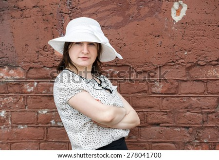 Female portrait in a retro style. Young woman in a white blouse and hat posing on a background old vintage brown brick wall. - stock photo