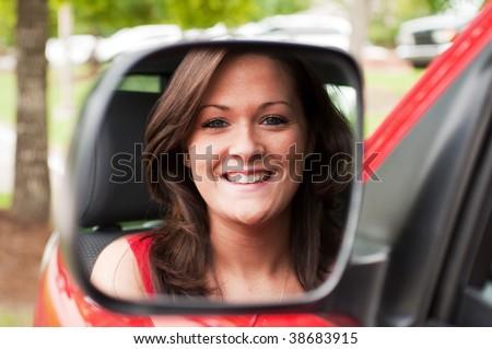 Female portrait of attractive brunette in vehicle mirror. - stock photo