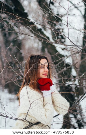 Female portrait outdoors serious expression. Young woman outside wearing warm winter clothing.  Winter portrait of young girl. Woman on the background falling snow in winter forest