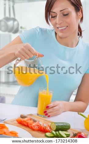 female pouring orange juice from jug - stock photo