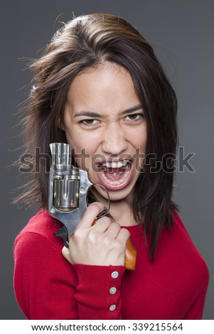 female power concept - enraged 20s multi-ethnic woman screaming in holding a handgun for revenge against aggression and violence
