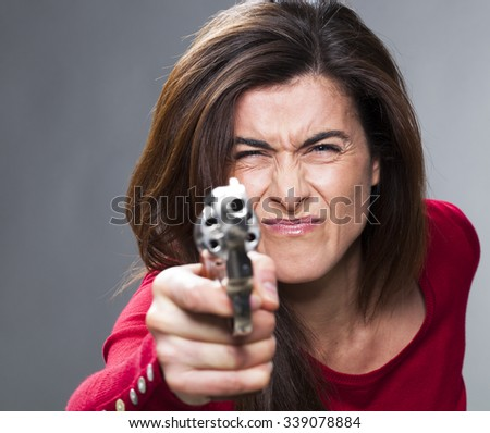 female power concept - near-sighted 30s brunette shooting with a handgun in foreground,training herself for self-defense or as a police officer,studio shot - stock photo