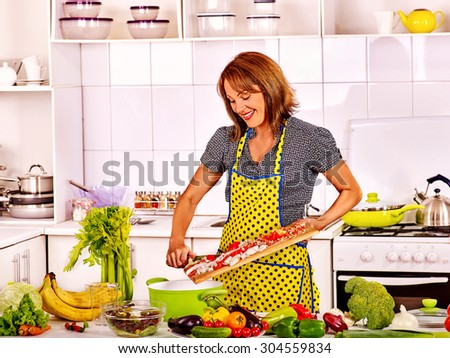 Female preparing food at kitchen. Woman cooking at home - stock photo