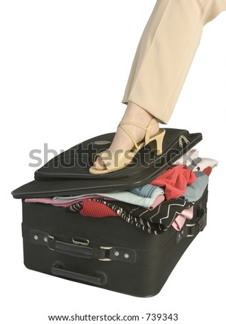 Female pressing down overfilled suitcase