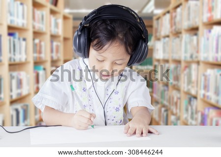 Female primary school student studying in the library while wearing headphones and write on the paper