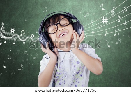 Female primary school student wearing glasses and smiling while listening music in the classroom - stock photo
