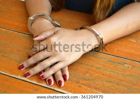 Female prisoner being investigated with hands cuffed on a table - stock photo