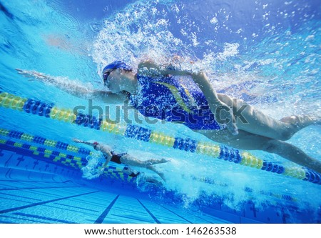 Female professional participants racing in pool - stock photo