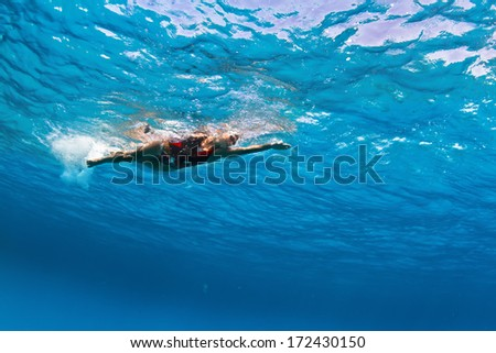 Female professional swimmer gushing through blue Red sea water with bubbles - stock photo