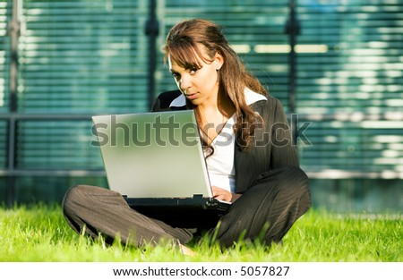 Female professional with a laptop on the lawn in front of a glass and steel facade