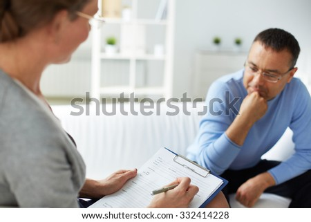 Female psychologist with document listening to man