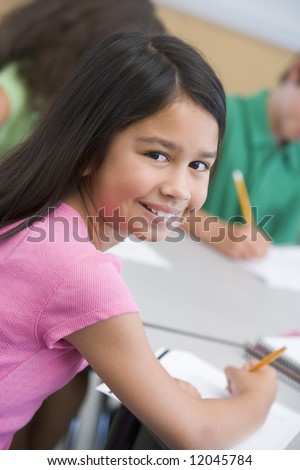 Female pupil in elementary school classroom writing