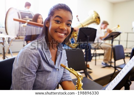 Female Pupil Playing Saxophone In High School Orchestra - stock photo