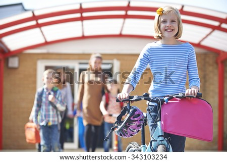 Female Pupil Pushing Bike At End Of School Day - stock photo