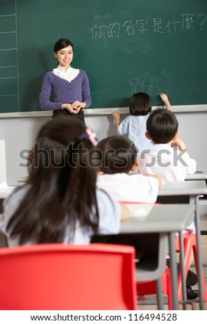 Female Pupil Writing On Blackboard In Chinese School Classroom