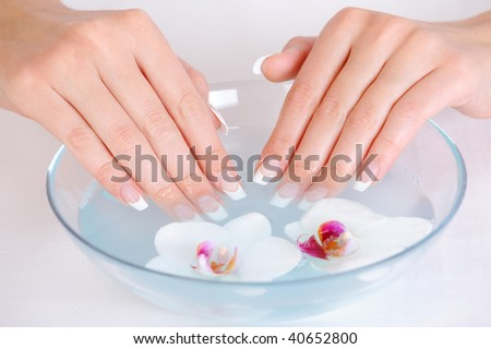 female putting her beautiful fingers into the bowl with water - spa treatment concept - stock photo