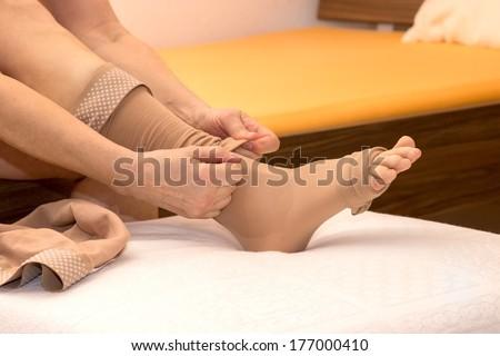 Female putting thrombosis stockings on - stock photo
