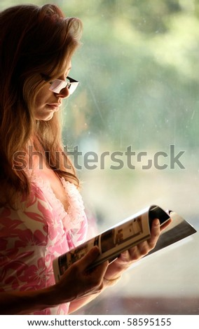 Female reading a magazine, window background ( free space on the right ) - stock photo