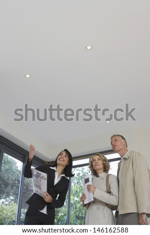 Female real estate agent and couple observing new property - stock photo