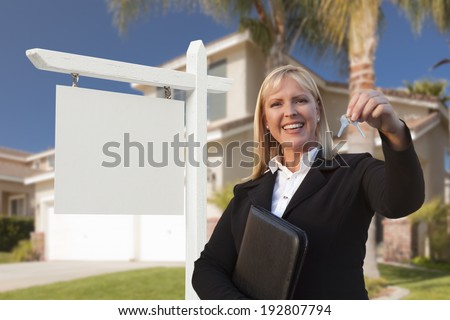 Female Real Estate Agent Handing Over the House Keys in Front of a Beautiful New Home and Blank Real Estate Sign. - stock photo