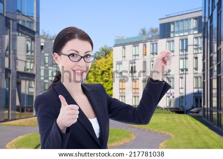 female real estate agent with key standing on street against modern building - stock photo