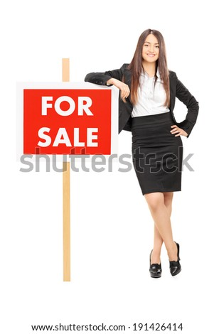 Female realtor leaning on a for sale sign isolated on white background - stock photo