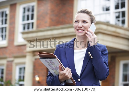 Female Realtor On Phone Outside Residential Property - stock photo