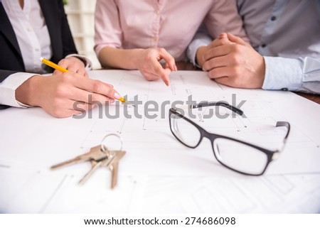Female realtor showing contract with floor layout in an apartment to a young couple. Close-up. - stock photo