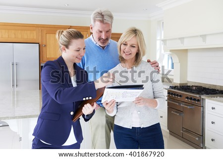 Female Realtor Showing Mature Couple Around New Home - stock photo