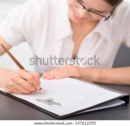 Female realtor signing mortgage contract in the office. Pretty smiling woman real estate seller reading partnership agreement with a house key lying on it.    - stock photo