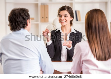 Female realtor with key and young couple from back. - stock photo