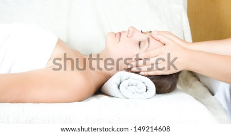 Female receiving massage therapy on face - stock photo