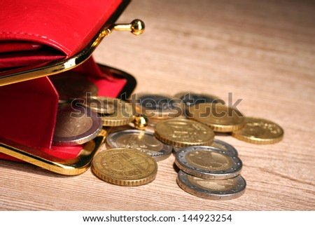 female red wallet with coins on wooden background - stock photo