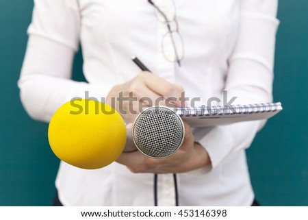 Female reporter or journalist at news conference, writing notes, holding microphones - stock photo
