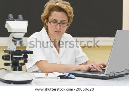 Female researcher analyzing data on a laptop in a laboratory.