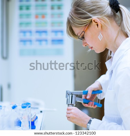 female researcher carrying out research experiments in a chemistry lab (color toned image) - stock photo