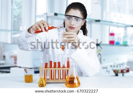 Female researcher doing research in the lab with red and orange chemical liquid on test tube